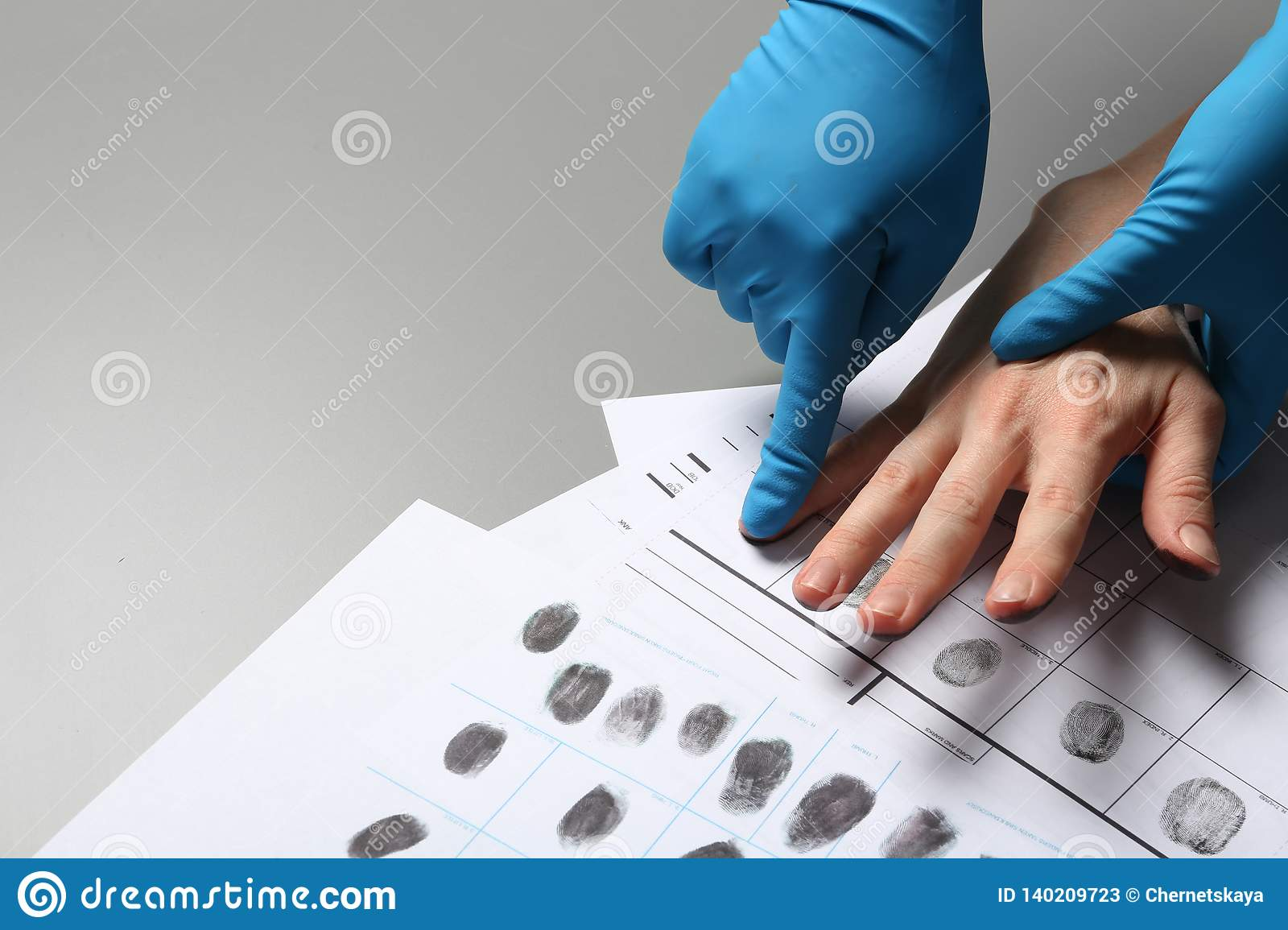 investigator-taking-fingerprints-suspect-grey-table-closeup-space-text-investigator-taking-fingerprints-suspect-140209723